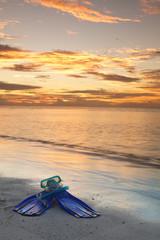 Pinne e maschera da sub su  una spiaggia.