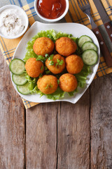 croquette balls with sauce on a plate. vertical top view