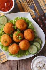 potato croquettes with lettuce and cucumber top view vertical