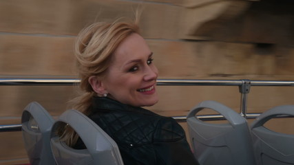 happy woman on holiday on double decker bus