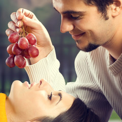 Portrait of young couple eating grapes, outdoor