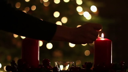 Female hand lighting a candle, slow motion