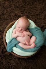 Sleeping Newborn in a Bowl