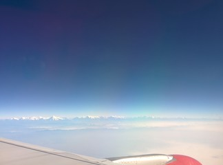 Blue sky with Himalayas range and airplane wings