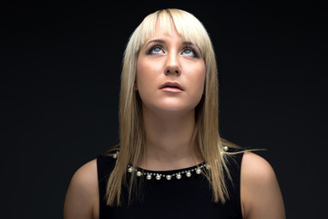 Photo of young blond woman looking up