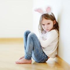 Angry little girl wearing bunny ears