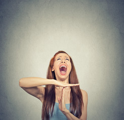 Young woman showing time out hand gesture frustrated