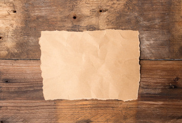 Piece of torn paper on old grunge wooden table