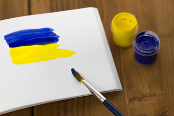 Painted Ukrainian flag on sketchbook with colorful paint tubes