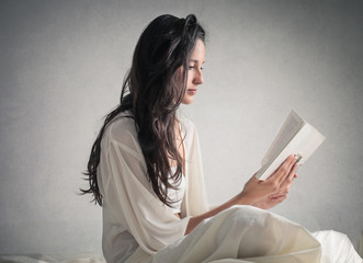 Girl in white reading a book