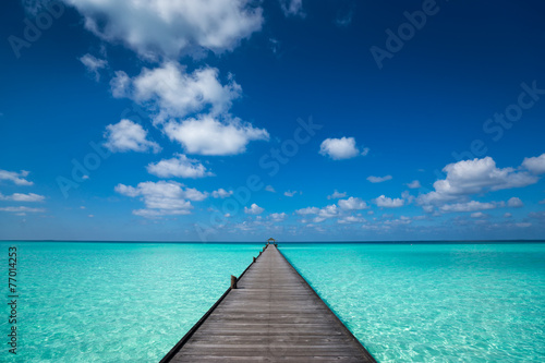 Papiers peints Plage Wooden pier with blue sea and sky background