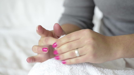Woman with painted nails uses nail polish remover