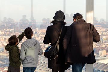 Famiglia osserva la città dalla finestra del grattacielo