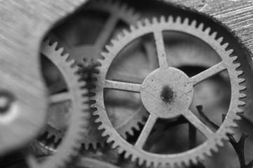Black and white background with metal cogwheels inside clockwork