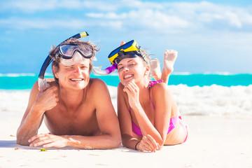 Beach travel couple having fun snorkeling, lying on summer beach