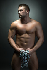 Naked muscular man posing with chain