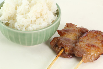 grilled pork and sticky rice on plate
