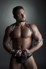 Image of strong male dancer posing with chain