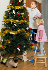Two little girls decorating Christmas tree
