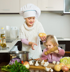 Two little sisters at home kitchen