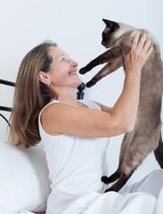 woman hugging a Siamese cat.
