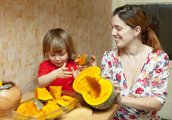 Happy mother with girl cooks pumpkin in kitchen