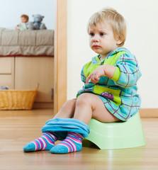 Baby girl sitting on potty