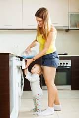 long-haired woman  and child using washing machine