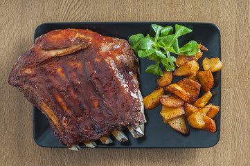 Barbecued honey ribs served with potatoes