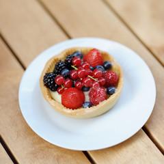 Custard fruit tart on white plate