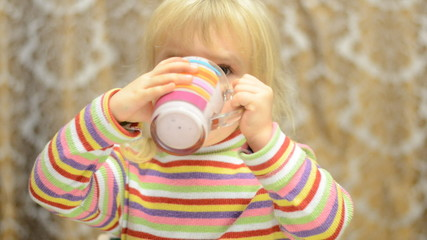 Little girl drinks emotionally and sign thumb up