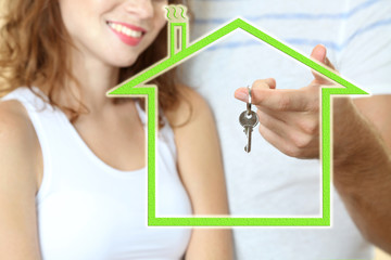 Loving couple with keys in drawing house
