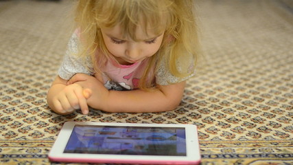 Cute Little Girl Works on Tablet Computer Lying on Carpet
