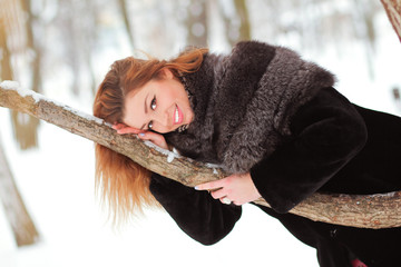 Pretty young girl lying on the winter tree