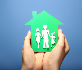 Cutout house with paper family in female hands