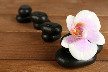 Spa stones with orchid on wooden background
