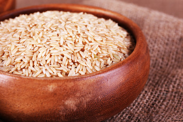 Brown rice in bowl on sackcloth background
