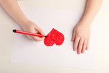 Fototapety Close-up of child hands drawing a red heart