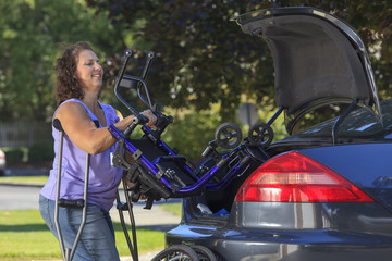 Woman with Spina Bifida putting wheelchair in trunk of car