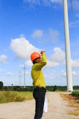 Woman engineer or architect with white safety hat and wind turbi