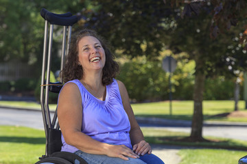 Woman with Spina Bifida laughing while sitting in wheelchair