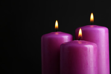 Purple candles on black background