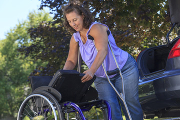 Woman with Spina Bifida assembles wheelchair for transport