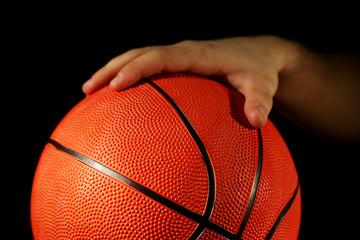 Basketball player holding ball, on dark background