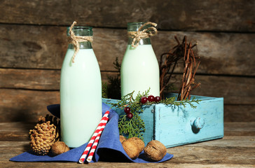 Bottles of fresh milk with natural decor, on wooden background