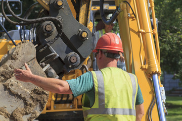 Construction foreman guiding excavator operator