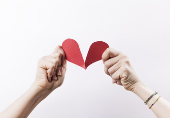 Woman hands tearing red paper heart