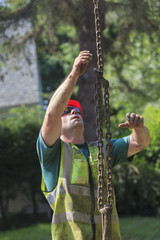 Construction worker guiding chain attached to excavator