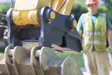 Construction worker observing excavator bucket