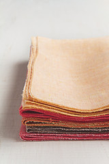 Stack of hand made colorful napkins on white background